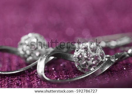 Luxury silver earrings are on pink background.