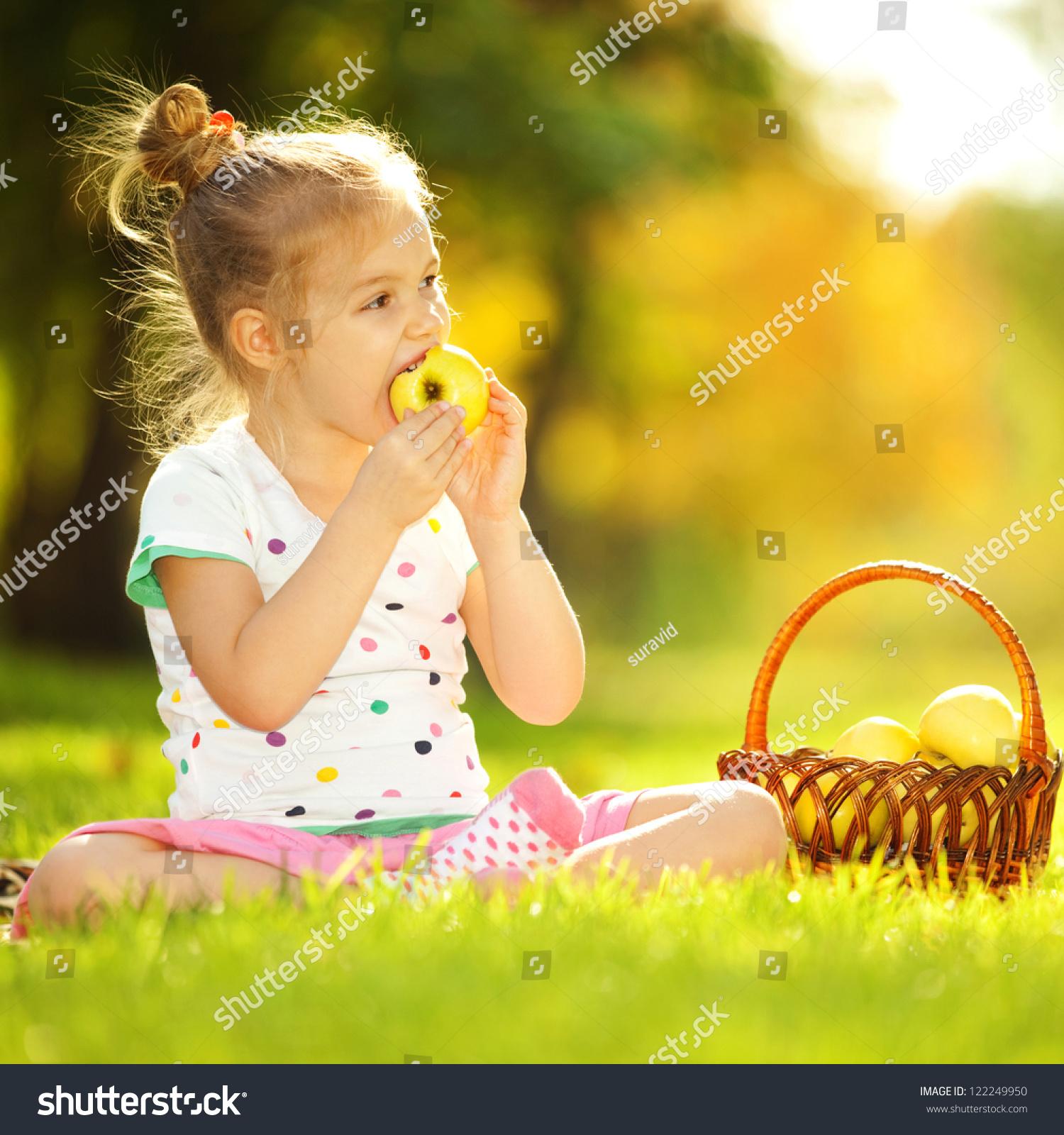 可爱的小女孩在公园里吃苹果