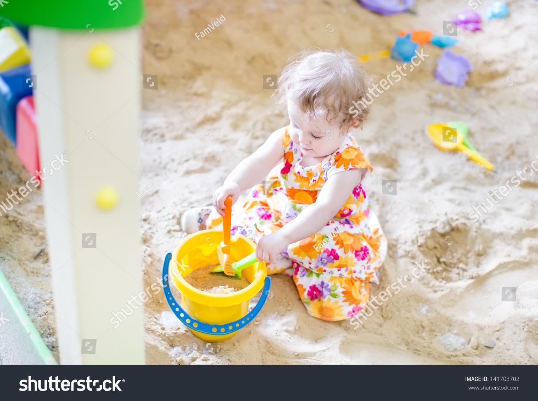 可爱的小女孩在操场上玩沙子
