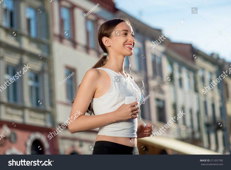 跑步者戴着耳机和智能手机的臂章.