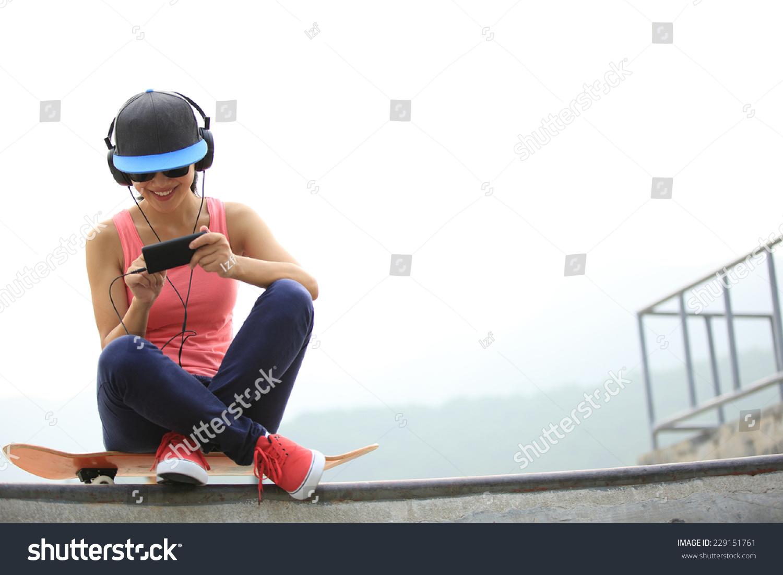女人滑板运动员从手机mp3播放器听音乐在滑板运动