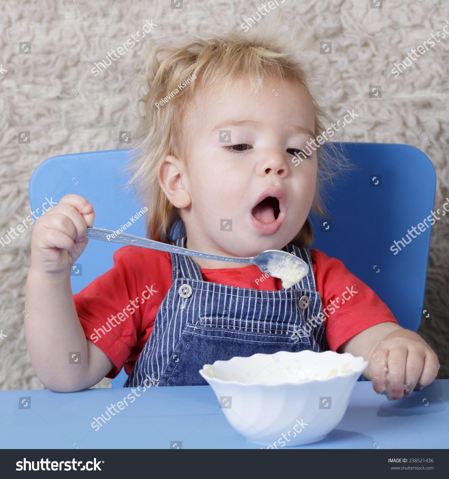 小孩子学着用勺子吃饭-食品及饮料