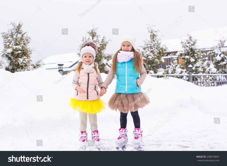 可爱的小女孩在滑冰在冬季下雪天的户外溜冰场-人物