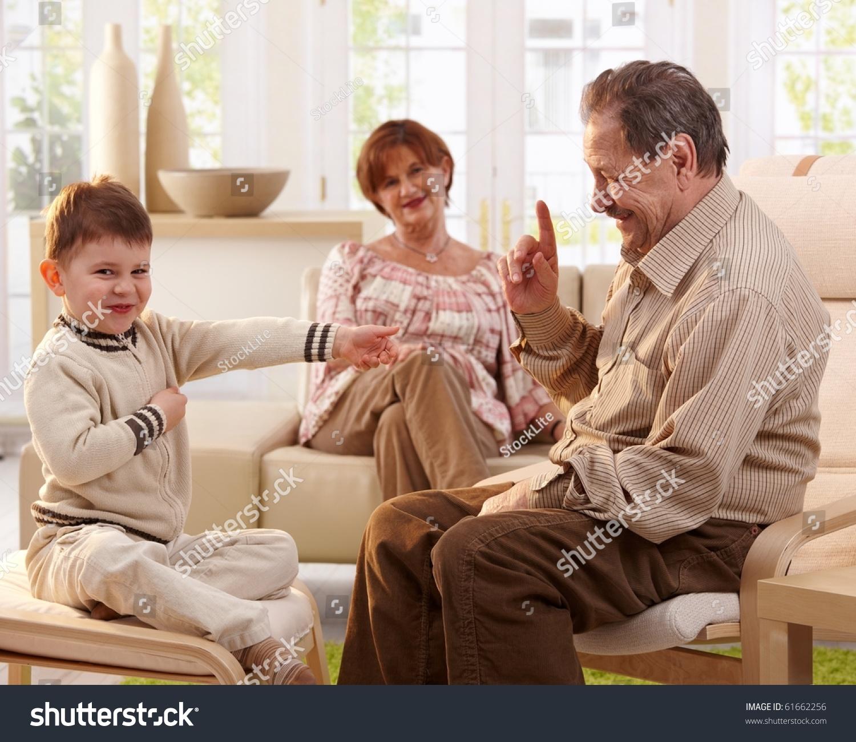 快乐微笑的爷爷讲故事他的孙子,奶奶听背景.-运动