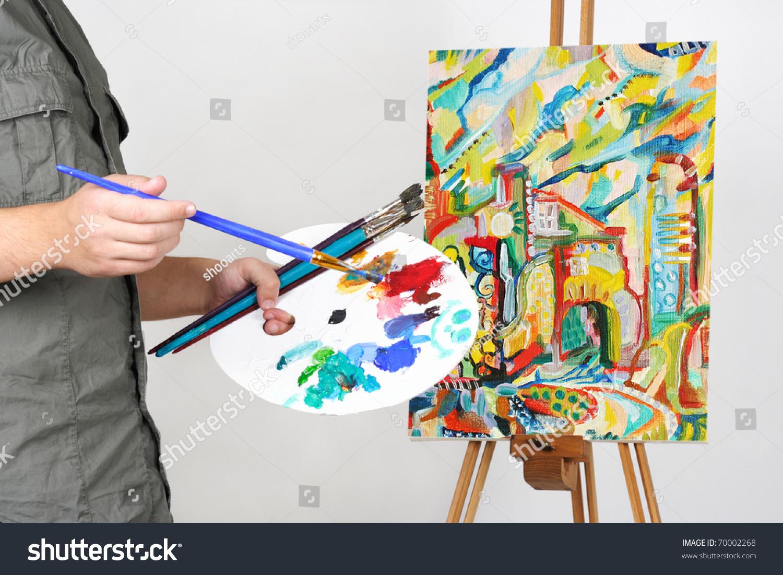 特写镜头的男人拿着画笔和调色板,绘画和抽象的城市